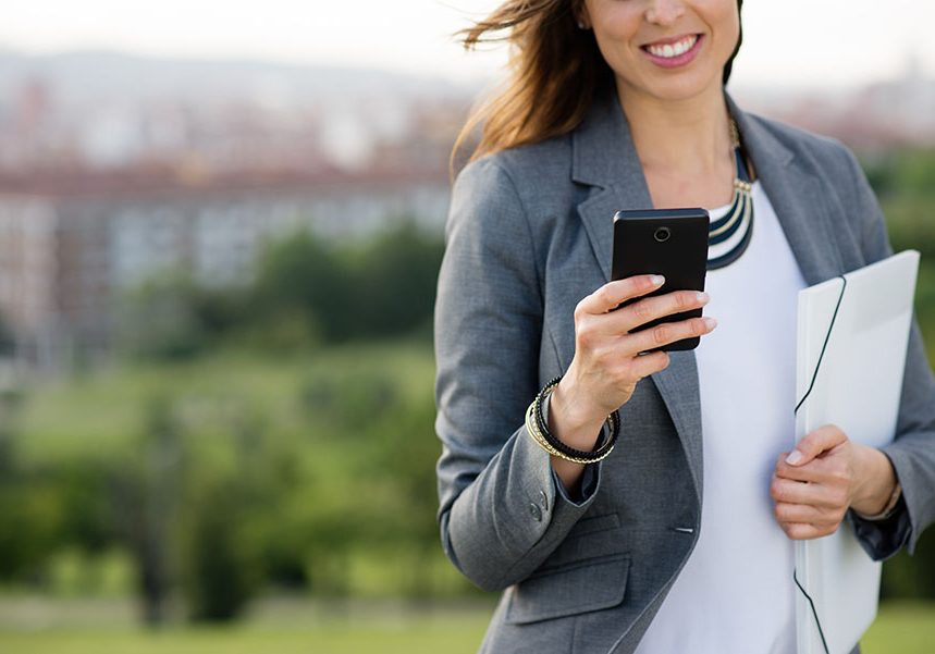 Businesswoman texting on smartphone. Female entrepreneur sending sms or checking business news on her cellphone outside.