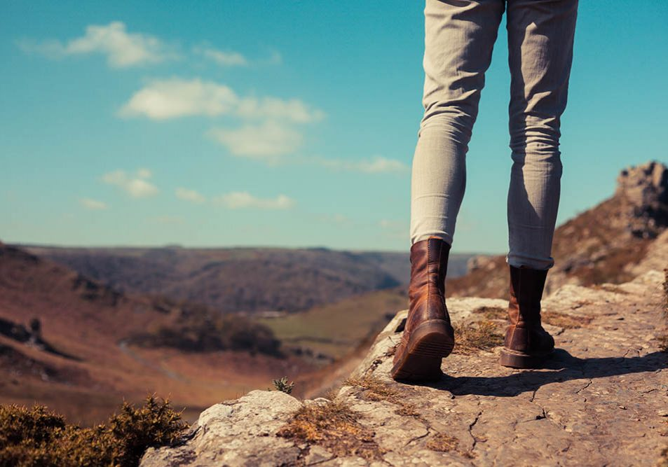 Closeup on a young woman's feet and legs as she is trekking in the mountains
