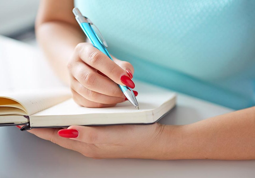 Young woman writes to black diary on a white table